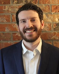 Picture of Gregory: Greg is smiling. He has brown curly hair and a beard. He is wearing a white collared shirt and navy jacket and stands in front of brick wall.